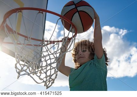 Healthy Children Lifestyle. Closeup Face Of Kid Basketball Player Making Slam Dunk