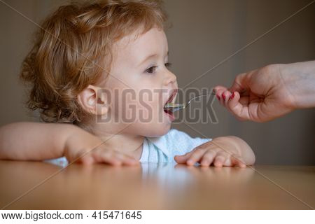 Spoon Feeding Baby. Mother Giving Healthy Food To Her Adorable Child At Home. Feeding Kids