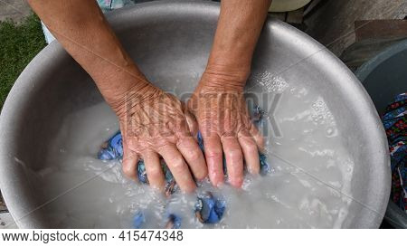 Senior Arms Of 80s Woman Crumple And Wash Clothes In Old Aluminium Basin With Soap Water. Obsolete W