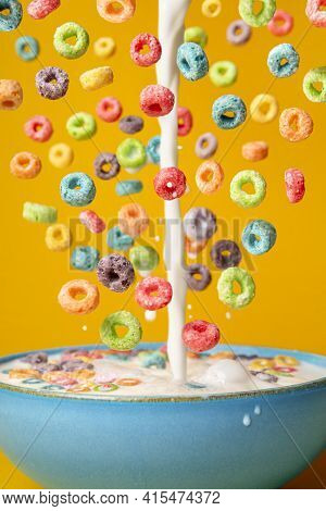 Dropping Cereals And Pouring Milk Into A Blue Bowl, Isolated On An Orange Background. Preparing Brea