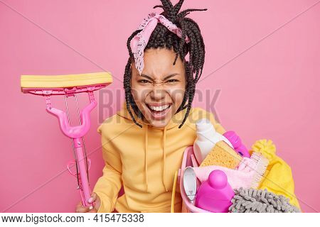 Emotional Dark Skinned Housewife Has Dreadlocks Exclaims And Smirks Face Poses With Cleaning Tools D