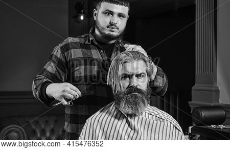 Brutal Man. Handsome Hairdresser Cutting Hair Of Male Client. Hairstylist Serving Client At Barber S