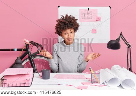 Hesitant Talented Female Architect Spreads Palms Poses Confused At Desktop Doesnt Know How To Improv