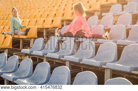 Leg Stretches. Teenage Girls Do Splits On Stadium Seats. Stretching Exercises. Stretching Routine