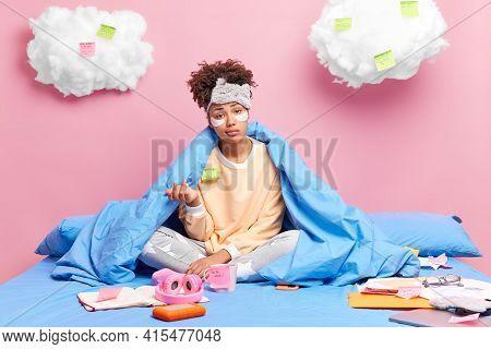Bored Puzzled Woman Looks Indignant At Camera Raises Palm Wears Pajama Sleepmask Sits In Lotus Pose
