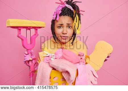 Indignant Displeased Afro American Woman Has Big Cleaning Day Holds Mop And Sponge Poses Near Basket