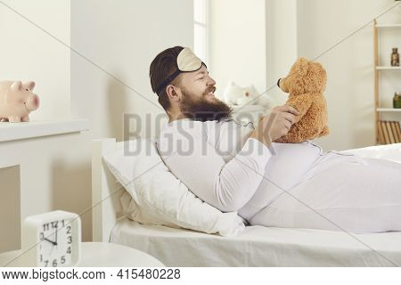 Cheerful Man In White Pajamas And A Sleeping Mask Woke Up And Behaves Like A Child.