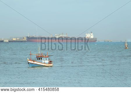 A Small Blue Fishing Boat Was Sailing In The Middle Of The Sea, Heading For The Shore. There Is A Sk