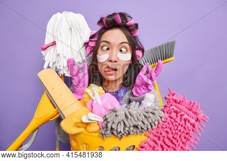 Funny Brunette Housewife Makes Funny Grimace Crosses Eyes Sticks Out Tongue Raises Hands In Gloves A