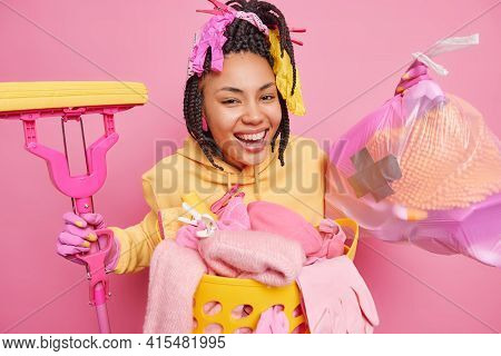 Cleaning Domestic Chores And Maintenance Concept. Positive Housewife With Dreadlocks Smiles Broadly