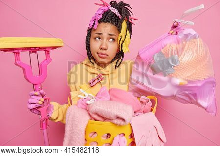 Spring Cleaning And Housekeeping Concept. Hesitant Displeased Dark Skinned Woman With Dreadlocks Col