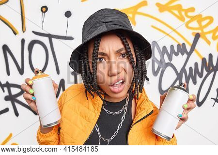 Discontent Teenage Girl With Braids Holds Aerosol Cans For Making Graffiti Dressed In Yellow Jacket