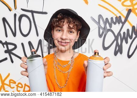 Pleased Man Being Graffiti Artist Holds Aerosol Color Cans Wears Hat And Orange T Shirt With Chains