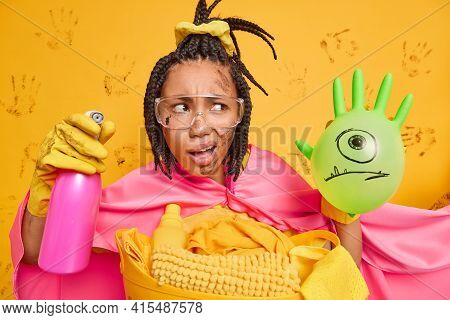 Puzzled Busy Dark Skinned Woman Maid Does Lot Of Work At Home Dressed In Superhero Costume Holds Cle
