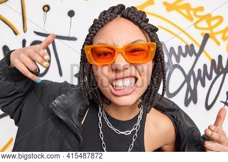 Cheeky Woman With Dreadlocks Clenches Teeth Makes Yo Gesture Feels Cool Belongs To Street Gang Wears