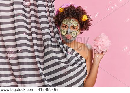 Serious Sulking Woman With Curly Afro Hair Wears Beauty Mask Cucumber Slices To Refresh Skin Stands