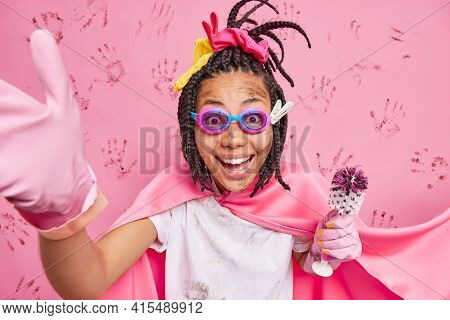 Happy Busy Super Housewife With Braids Wears Goggles Cape And Rubber Gloves Smiles Positively Holds