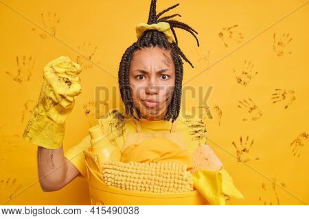 House Cleaning Concept. Annoyed African American Woman Clenches Fist Looks Angrily At Camera Poses D