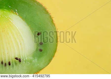 Close Up Green Kiwi On Yellow Background With Place For Text
