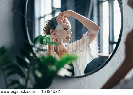 Treat For Dull And Tired Skin. Woman Applies Sheet Mask To Her Face.