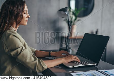 Woman Sitting And Working At Workplace With Laptop.