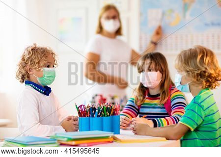 Teacher In Class, School Child In Face Mask During Corona Virus And Flu Outbreak. Boy And Girl Back