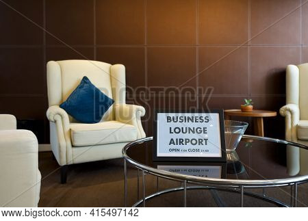 The Business Lounge Airport Service Time Sign Is Placed On A Modern Round Tempered Glass Table.