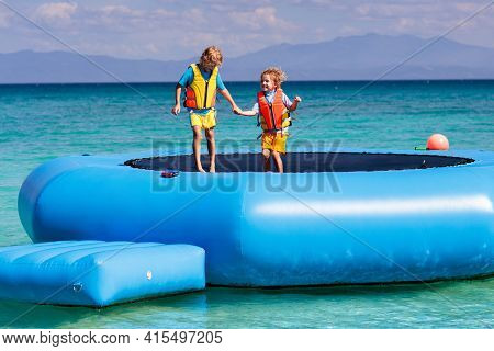 Kids Jumping On Trampoline On Tropical Sea Beach. Children Jump On Inflatable Water Slide.