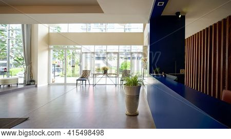 A Long Dark Blue Reception Counter Is Located Beside The Hotel Lobby.