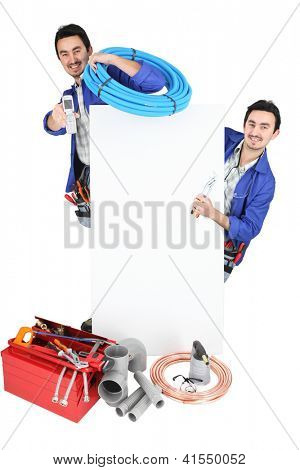 Plumber stood by advertising poster