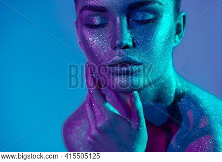 High Fashion model woman in colorful bright silver sparkles and neon lights posing in studio, portrait of beautiful sexy girl, trendy glowing sequins make-up. Art design make up. Glitter Vivid makeup.