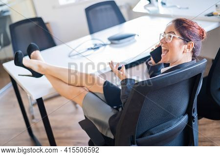 Business Woman Folded Her Legs At The Office Desk And Talking On A Cell Phone. Boredom At Work.