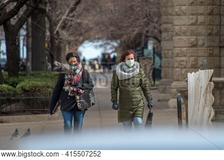 Chicago, Il March 14, 2021, Two Women Walking Down The Sidewalk Wearing Masks Due To The Covid 19 Pa