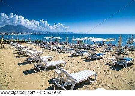 Alanya, Turkey -October 20, 2020: People relaxing on the sandy beach in Alanya,  Turkey.