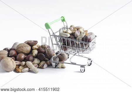 A Cart Full Of Different Nuts And A Mountain Of Nuts On A White Background Of Assorted Nuts