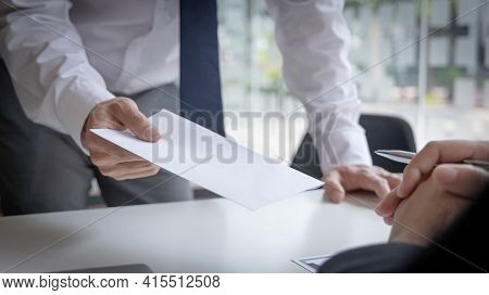 Employee handed over a document envelope and a box of work equipment beside him, Businessman submits
