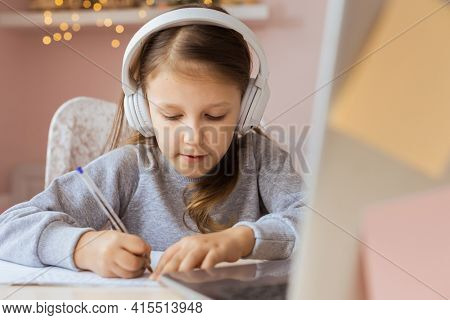 Schoolgirl Girl Studies Online On Laptop At Home. Communicates Online With Teacher. Teaches Lessons From School At Computer. Participates In Distance Education.