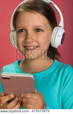 Little Beautiful Baby Girl Pink Background Bright Clothes Yellow Pants Turquoise Blue Shirt Wearing White Headphones Listening To Music With Smartphone In Hand