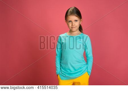 Little Beautiful Baby Girl Pink Background Bright Clothes Yellow Pants Turquoise Blue Shirt Looks Into The Camera