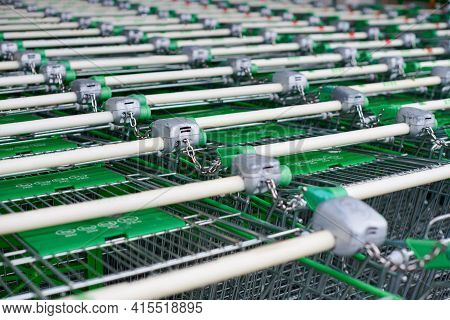 Row Of Parked Trolleys In Supermarket. Many Empty Green Shopping Carts In Row.