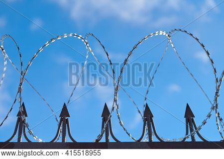 Barbed Wire On Fence, Steel Grating Fence, Metal Fence Wire. Coiled Razor Wire With Sharp Steel Barb
