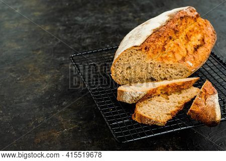 Sliced Loaf Of Homemade Wheat Bread On A Black Wire Rack Against A Dark Concrete Background.