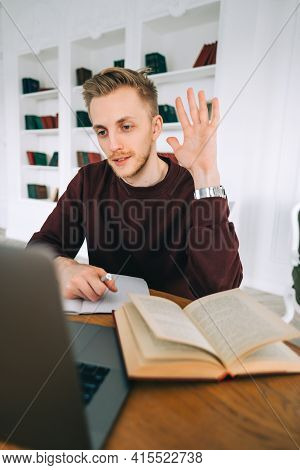 Young Caucasian Man College Student Studying With Books, Laptop Distantly At Home Library Using Vide