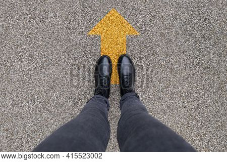 Black Shoes Standing On The Asphalt Concrete Floor With Yellow Direction Arrow Symbol. Moving Forwar
