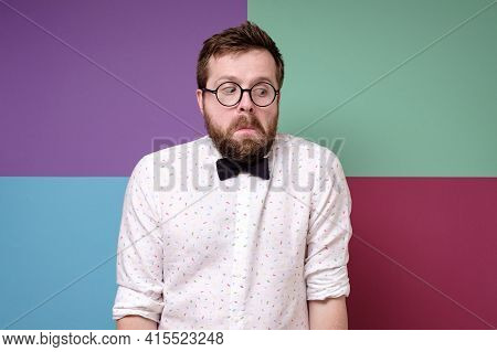 Bizarre Man In Round Glasses, A Shirt And A Bow Tie Hunched Shoulders In Bewilderment And Looks Down
