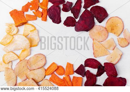 Dried Vegetable Chips Framing Copy Space In The Middle. Pumpkin, Carrot, Potato, Beet And Turnip Sli