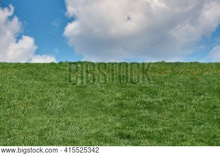 Green Fresh Grass Under Blue Sky With Cloud In Summer Day. Landscape View Of Green Grass On Slope Wi