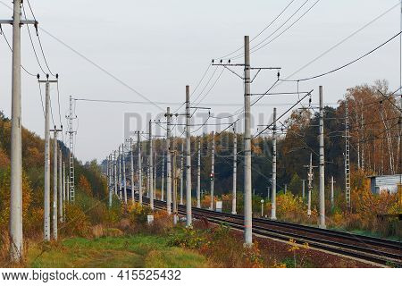 Perspective Of Railway Tracks With Many Electricity Pylons. Two Railroad Tracks Running Through Autu