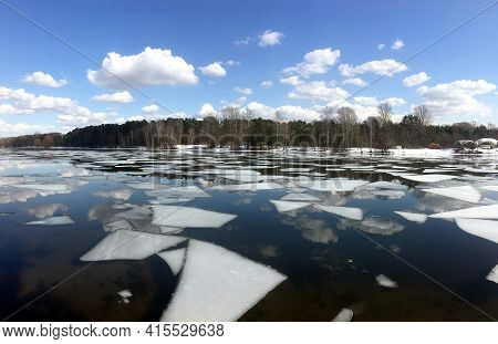 Beautiful Natural Landscape With Ice Floes Adrift On The Spring River And Forest Trees On Opposite B