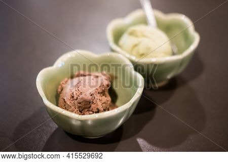 Ice Cream Scoops Chocolate Flavor In Green Cup And Green Tea Flavor Background. Selective Focus